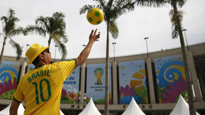A street busker throws a soccer ball in the air outside the Maracana stadium in Rio de Janeiro ahead of the 2014 World Cup, June 6, 2014. (Reuters/Paul Hanna)