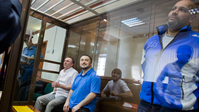 Suspects in the murder case of Russian investigative journalist Anna Politkovskaya, Rustam Makhmudov (2nd L), who is suspected of gunning down the renowned journalist and Kremlin critic Anna Politkovskaya, and his co-defendants, Lom-Ali Gaitukayev (L), who is accused of organising the crime along with former Moscow police officer, Sergei Khadzhikurbanov (R), looking on from a glass cage in Moscow's City Court.(AFP Photo / Evgeny Feldman)