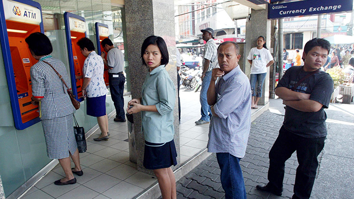 Thai bank clients queue to withdraw money from ATMs in Bangkok (AFP Photo)