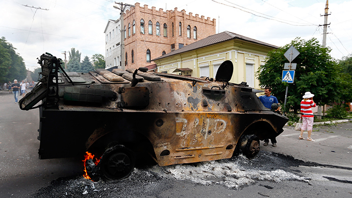 Residents look at a destroyed armoured personnel carrier of the DNR (Donetsk People's Reublic) at the site of fighting in the eastern Ukrainian port city of Mariupol June 13, 2014 (Reuters / Shamil Zhumatov)