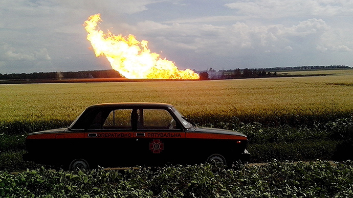 This handout picture taken and released by the Ukrainian Emergency Service on June 17, 2014 shows a police car parked beside a field near a fire on the gas pipeline the village of Iskivtsi in the Lokhvytsia region (AFP Photo)