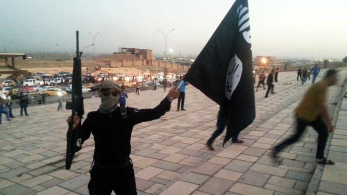 A fighter of the Islamic State of Iraq and the Levant (ISIL) holds an ISIL flag and a weapon on a street in the city of Mosul, June 23, 2014. (Reuters / Stringer)