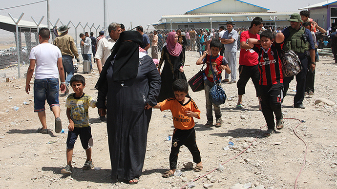 Families fleeing the violence in the Iraqi city of Mosul wait at a checkpoint in outskirts of Arbil, in Iraq's Kurdistan region, June 10, 2014 (Reuters / Azad Lashkari)