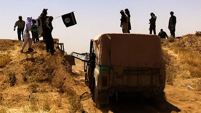 A file image made available by the jihadist Twitter account Al-Baraka news on June 9, 2014 allegedly shows Islamic State of Iraq and the Levant (ISIL) militants waving the trademark Jihadits flag as vehicles drive on a newly cut road through the Syrian-Iraqi border between the Iraqi Nineveh province and the Syrian town of Al-Hasakah. (AFP Photo)