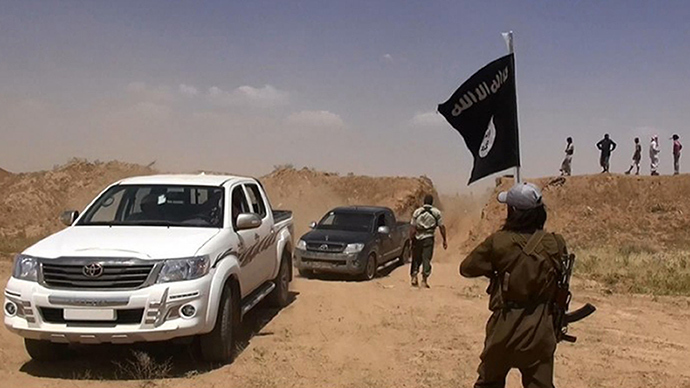 A militant of the jihadist group Islamic State of Iraq and the Levant (ISIL) waving the Islamic Jihad flag as vehicles drive on a newly cut road through the Syrian-Iraqi border (AFP Photo / Albakara News)