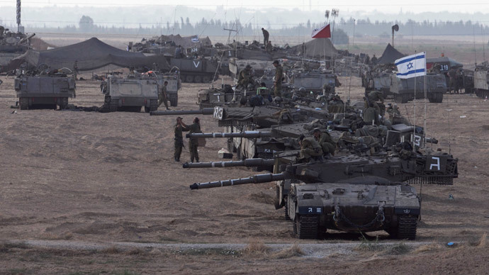 Israeli tanks and armoured personnel carriers (APCs) are seen at a staging area outside the central Gaza Strip July 15, 2014. (Reuters / Baz Ratner)
