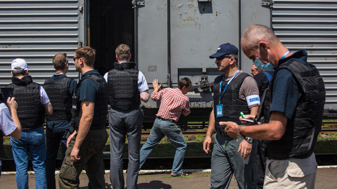 OSCE mission members at the rail station in the town of Torez before the departure of the train carrying the bodies of the Boeing 777 plane crash victims for Donetsk. (RIA Novosti / Andrey Stenin)