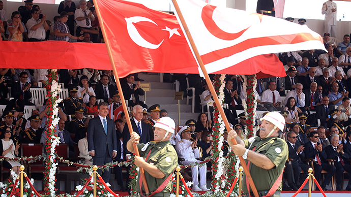 Turkish Cypriot war veterans march with Turkish and Turkish Cypriot flags, past Turkish President Abdullah Gul (back L) and Turkish Cypriot leader Dervis Eroglu, during a military parade celebrating 40 years since Turkey invaded Cyprus, in Nicosia July 20, 2014 (Reuters / Andreas Manolis)