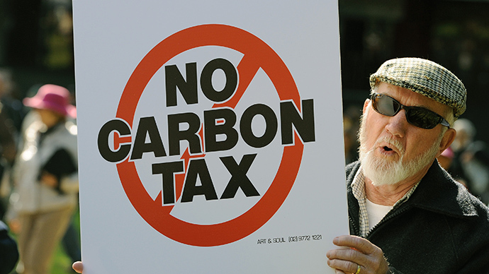 A protester holds a placard during a no carbon tax rally in Sydney. (AFP Photo / Greg Wood)