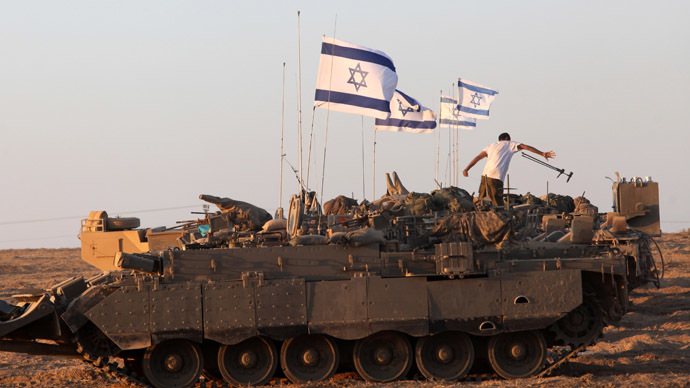 Israeli soldiers work on their an armoured personnel carrier (APC) as they are stationed along the border between Israel and the Hamas-controlled Gaza Strip on July 26, 2014. (AFP Photo)