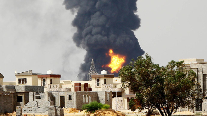 A picture taken on July 28, 2014 shows flames and smoke billowing from an oil depot where a huge blaze started following clashes around Tripoli airport, in southern Tripoli. State-owned National Oil Corp has warned of a humanitarian and environmental catastrophe after the tank containing six million litres of fuel was set ablaze by rocket fire late on July 27, 2014. (AFP Photo / Mahmud Turkia)