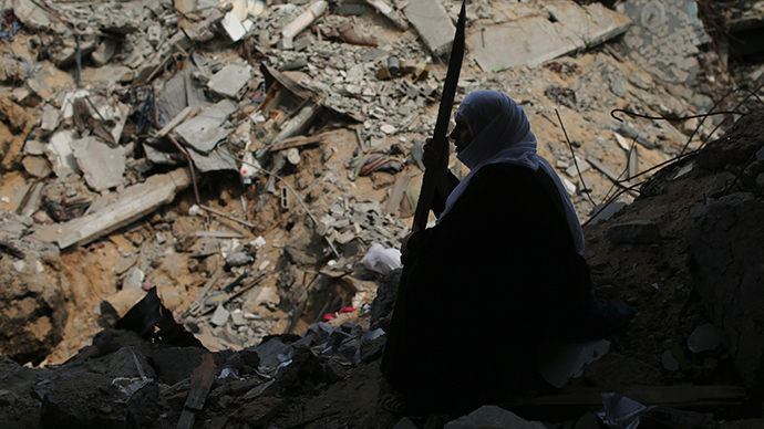 A Palestinian woman sits next to her destroyed house after returning to it in the Shejaia neighborhood, which witnesses said was heavily hit by Israeli shelling and air strikes during an Israeli offensive, in the east of Gaza City August 5, 2014 (Reuters / Mohammed Salem)