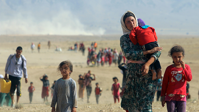 Displaced people from the minority Yazidi sect, fleeing violence from forces loyal to the Islamic State in Sinjar town, walk towards the Syrian border, on the outskirts of Sinjar mountain, near the Syrian border town of Elierbeh of Al-Hasakah Governorate August 11, 2014 (Reuters / Rodi Said)