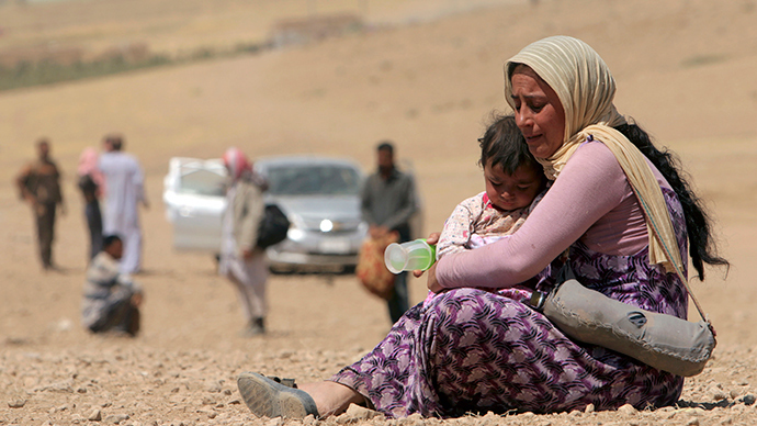 A displaced woman and child from the minority Yazidi sect, fleeing violence from forces loyal to the Islamic State in Sinjar town, rest as they make their way towards the Syrian border, on the outskirts of Sinjar mountain, near the Syrian border town of Elierbeh of Al-Hasakah Governorate August 10, 2014 (Reuters / Rodi Said)