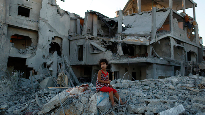 A girl sits on the ruins of her family's home that witnesses say was destroyed by Israeli airstrikes in the Beit Hanoun neighbourhood of Gaza City, August 12, 2014 (Reuters / Siegfried Modola)