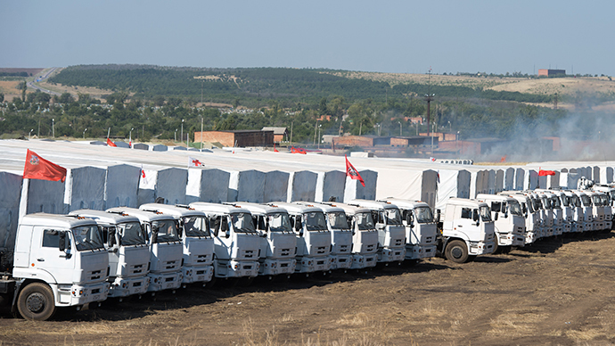 Trucks of Russian humanitarian convoy are parked in a field outside the town of Kamensk-Shakhtinsky in Rostov region, some 30 km from the Russian-Ukrainian border, Russia, on August 15, 2014. (AFP Photo / Dmitry Serebryakov)