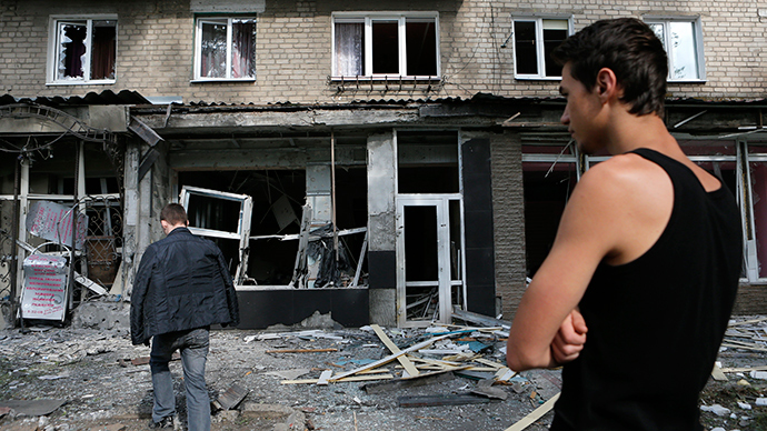 Local residents stand in front of an apartment block damaged by recent shelling in the settlement of Makiivka, on the outskirts of Donetsk, August 19, 2014 (Reuters / Maxim Shemetov)
