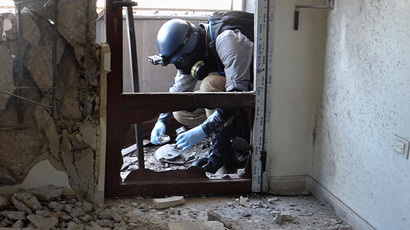 ARCHIVE PHOTO: A United Nations (UN) arms expert collects samples on August 29, 2013, as they inspect the site where rockets had fallen in Damascus' eastern Ghouta suburb during an investigation into a suspected chemical weapons strike near the capital (AFP Photo)