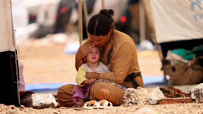 A refugee woman from the minority Yazidi sect, who fled the violence in the Iraqi town of Sinjar, sits with a child inside a tent at Nowruz refugee camp in Qamishli, northeastern Syria August 17, 2014 (Reuters / Rodi Said)