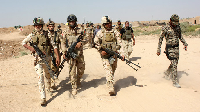 Iraqi security forces and Iraqi Shi'ite volunteers carry their weapons during an intensive security deployment to fight against militants of the Islamic State, formerly known as the Islamic State of Iraq and the Levant (ISIL), on the outskirt of Sulaiman Pek town in Salahuddin province, August 31, 2014. (Reuters / Stringer)
