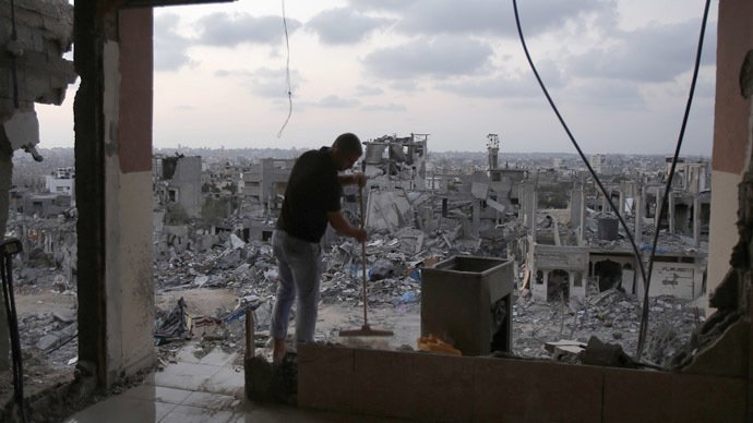 A Palestinian man cleans his house that witnesses said was heavy shelled by Israel during the offensive, in the Shejaia neighbourhood east of Gaza City August 31, 2014. (Reuters/Suhaib Salem)