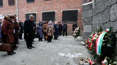 Polish President Bronislaw Komorowski (C) bows as he lays a wreath at the 'Wall of Death' in the former Nazi German concentration and extermination camp Auschwitz in Oswiecim January 27, 2015.(Reuters / Laszlo Balogh)
