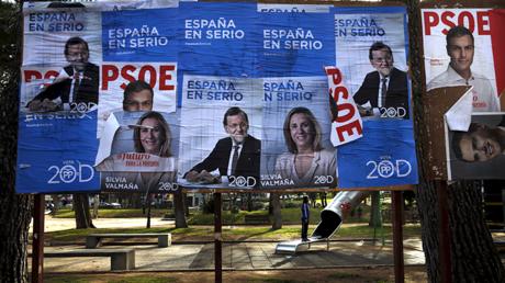 Carteles electorales para los próximos comicios del 20 de diciembre en España, junto a un parque donde juega una niña.