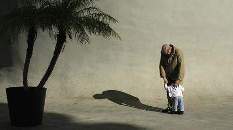 Un anciano abraza a un niño en la capital andaluza de Sevilla, España