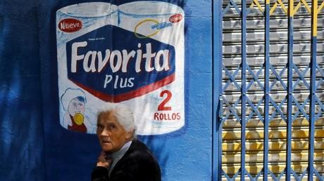 Una mujer jubilada pasa al lado de un cartel publicitario de papel higiénico