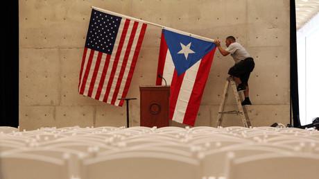 Un trabajador quita la bandera estadounidense y de Puerto Rico tras un mitin de Bernie Sanders, precandidato demócrata a la presidencia de EE.UU., en San Juan, Puerto Rico, el 16 de mayo de 2016.