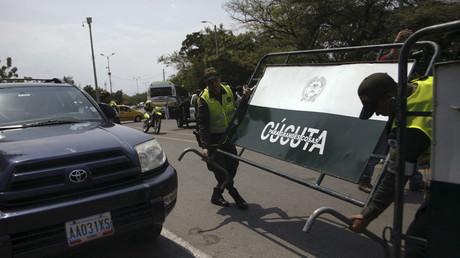 Policías colombianos llevan vallas cerca de coches que están cruzando a Venezuela por el puente internacional Francisco de Paula Santander en Escobal, Colombia, 27 de febrero de 2016.