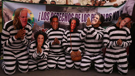 Manifestantes disfrazados de políticos peruanos presos protestan contra la empresa Odebrecht en Lima, Perú