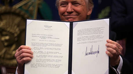 El presidente estadounidense, Donald Trump, mostrando un texto con su rúbrica