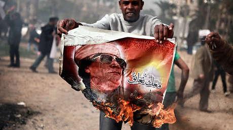 Un hombre quema un retrato de Muammar Gaddafi en Bengasi, Libia