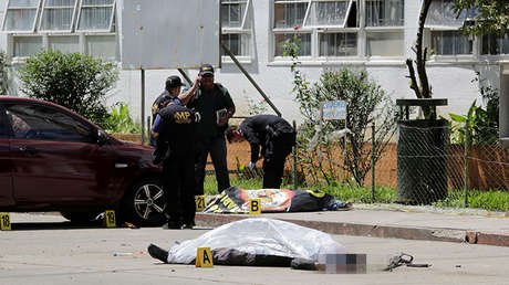 Elementos de la Policía permanecen junto a dos cadáveres luego que presuntos miembros de la Mara Salvatrucha atacaron el Hospital Roosevelt en Ciudad de Guatemala este miércoles.