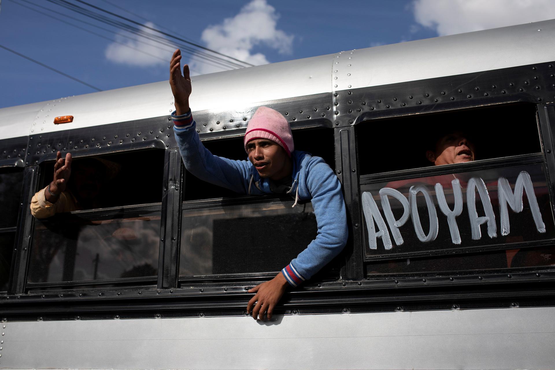Un hombre saluda a miembros de la caravana en el traslado a otro refugio de Tijuana.
