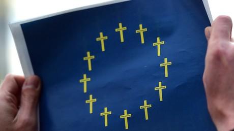 Ein Aktivist von Amnesty International hält ein Bild der europäischen Flagge hoch, das aus Trauerkreuzen besteht anstelle der gewöhnlichen goldenen Sterne.