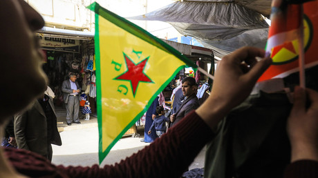 Ein Händler fixiert eine Flagge der YPG auf seinem Stand auf einem Markt in der nordöstlichen syrischen Stadt Qamischli auf, 20. März 2018.