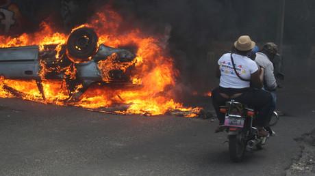 Menschen auf einem Motorrad fahren an einem brennenden Auto vorbei, Port-au-Prince, Haiti.