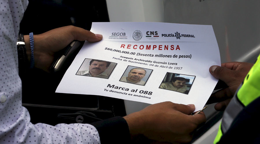 "A federal police  hand out flyers with photos of drug lord Joaquin ""El Chapo"" Guzman © Keith Bedford"