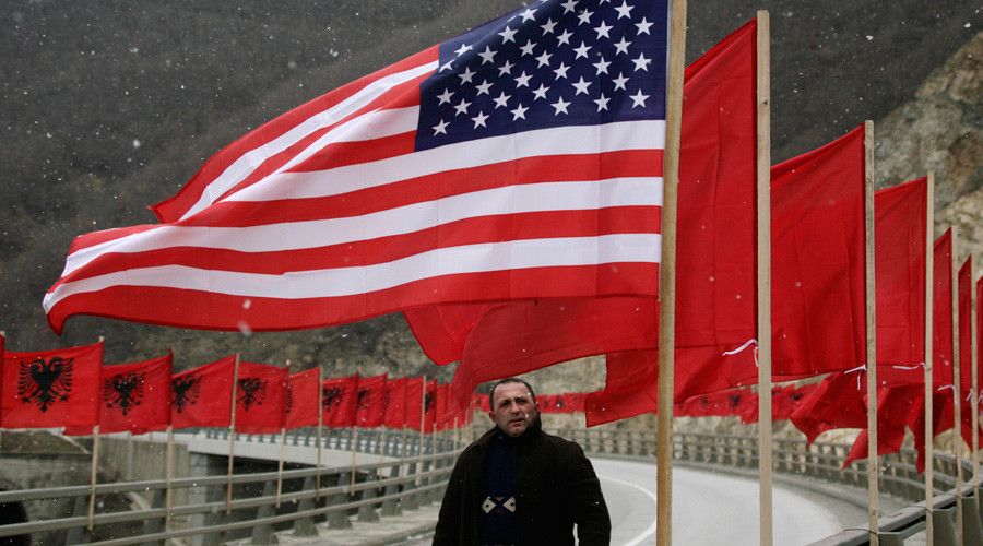 ARCHIVE PHOTO: A man walks down a road where Albanian and U.S. national flags have been put up ahead of the first anniversary of Kosovo's independence in the town of Kacanik, southeast of the capital Pristina February 15, 2009. © Hazir Reka