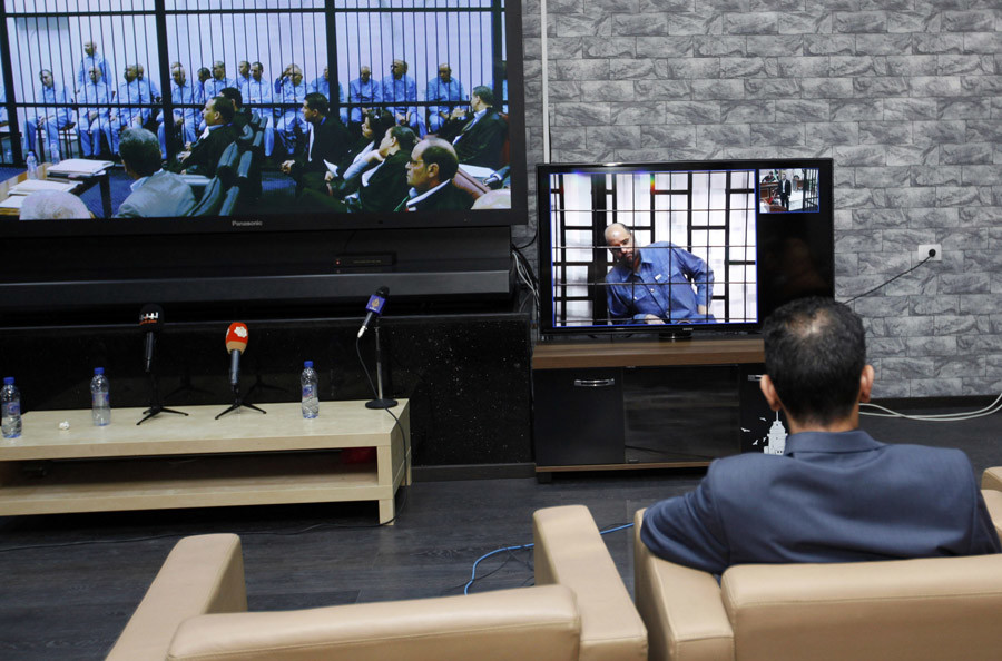 A man sits in front of two screens showing Saif al-Islam Gaddafi (R), son of late Libyan leader Muammar Gaddafi, via video-link from a courtroom in Zintan, as well as former officials from the Gaddafi government during a hearing at a courtroom in Tripoli, May 11, 2014. © Ismail Zitouny