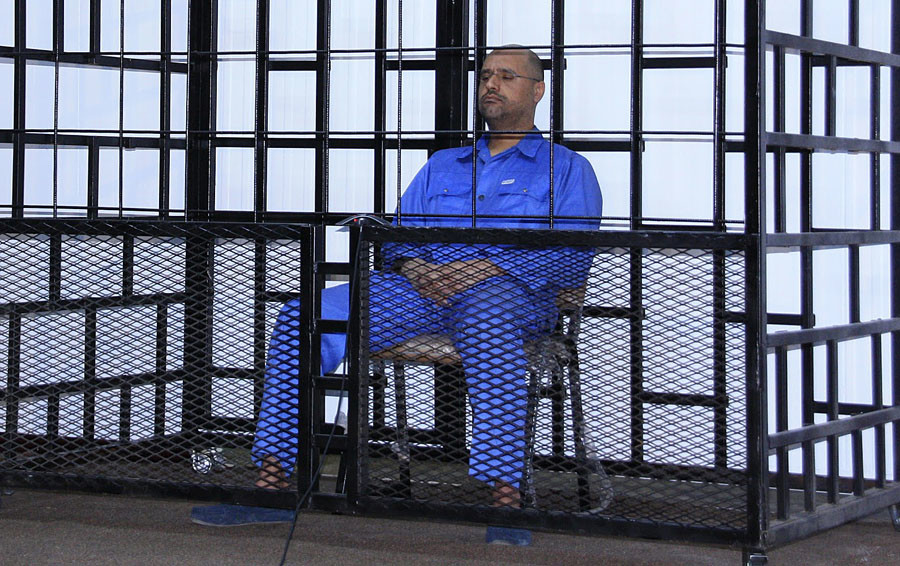 Saif al-Islam Gaddafi, son of late Libyan leader Muammar Gaddafi, attends a hearing behind bars in a courtroom in Zintan May 25, 2014. © Stringer