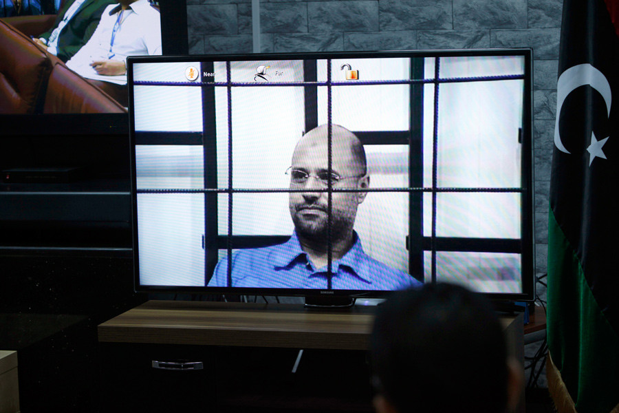 Saif al-Islam Gaddafi, son of deposed leader Muammar Gaddafi, is seen on a screen via video-link in a courtroom in Tripoli as he attends a hearing behind bars in a courtroom in Zintan, April 27, 2014. © Ismail Zitouny