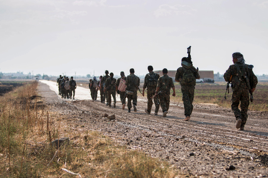 Kurdish fighters walk carrying their weapons towards Tel Abyad of Raqqa governorate © Rodi Said