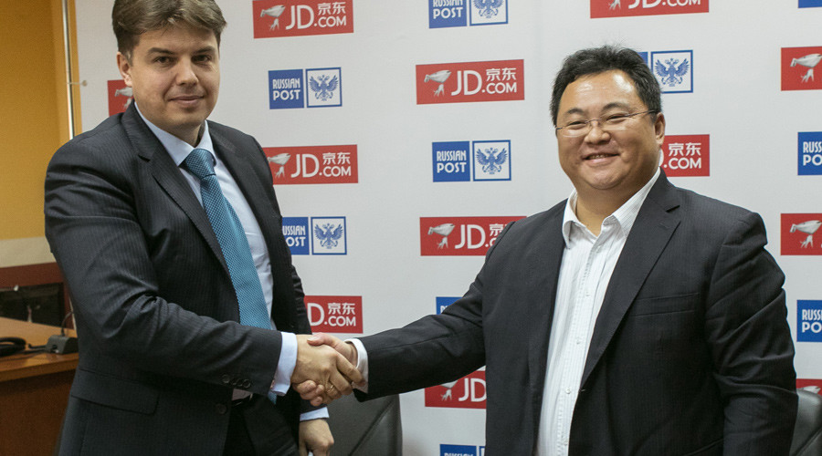 Deputy Director-General of Russian Post Sergey Malyshev (L) and JD.com CEO of International business unit Victor Xu at the signing ceremony Wednesday in Moscow