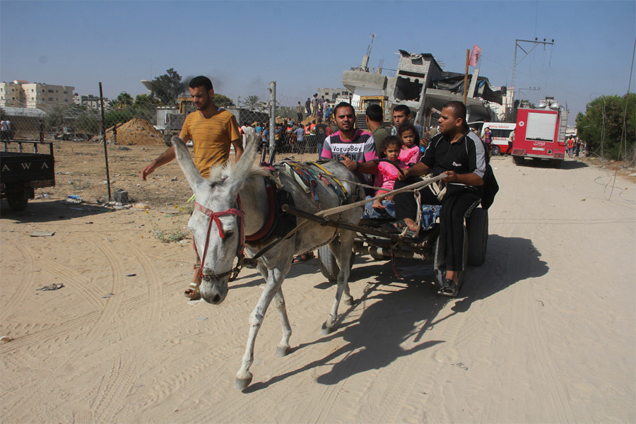 A Palestinian family returning to their home in eastern Rafah during the ceasefire, with the ruins of the house of the Abu Omran family in the background, on 1 August 2014 around 8am. © Private.