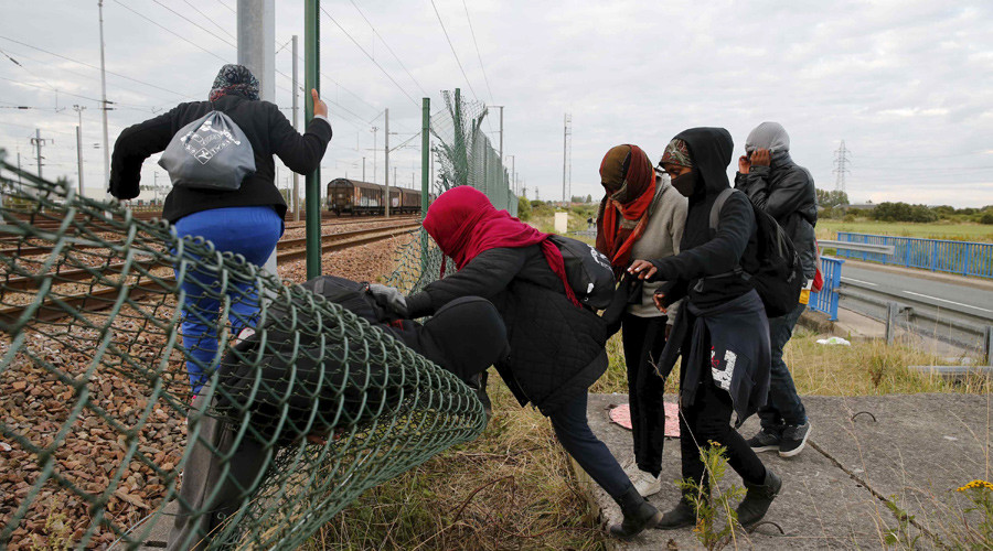 Migrants make their way across a fence near near train tracks as they attempt to access the Channel Tunnel in Frethun, near Calais, France, July 29, 2015. © Pascal Rossignol
