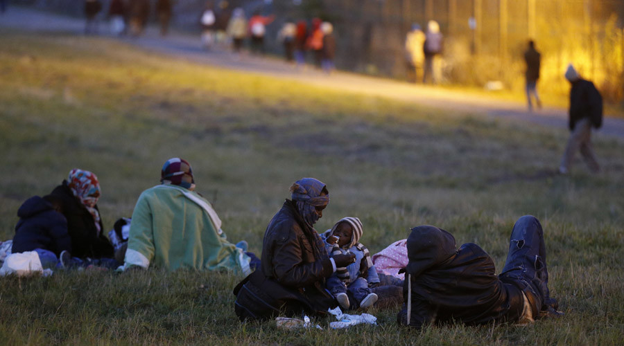 A migrant mother holds her child as she sits on the grass with other migrants at nightfall in Coquelles, near Calais, France. © Pascal Rossignol
