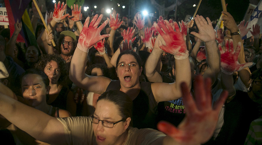 Protesters hold up gloves covered in red during a protest against the violence towards the gay community in Tel Aviv August 1, 2015 © Baz Ratner